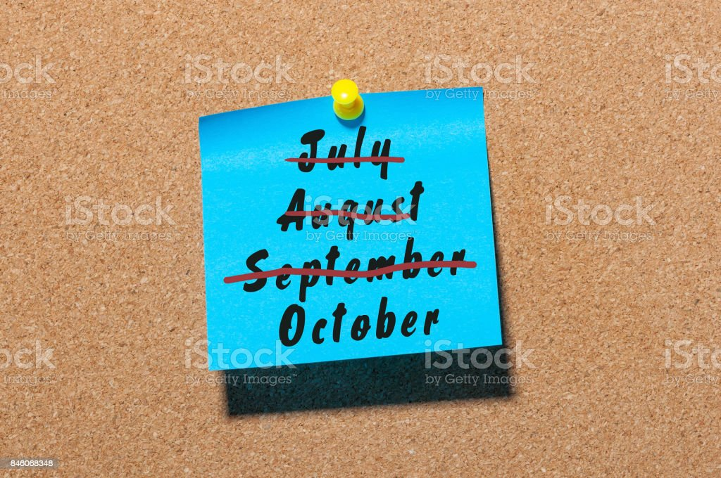 October beginning concept written at paper pinned on cork notice board background. Striked July, August, September stock photo