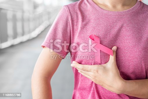 istock October Breast Cancer Awareness month, Woman in pink T- shirt with Pink Ribbon for supporting people living and illness. Healthcare, International women day and World cancer day concept 1168852786