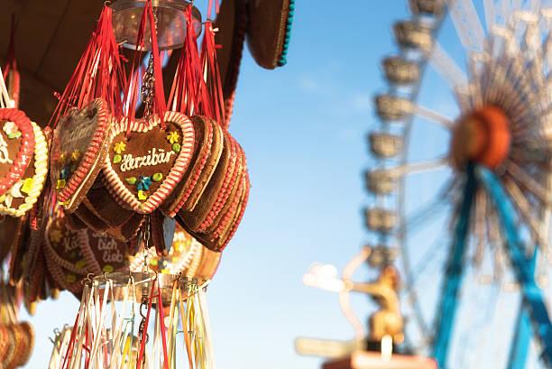 octoberfest gingerbread hearts hanging in front of ferris wheel - lebkuchenherzen stock-fotos und bilder