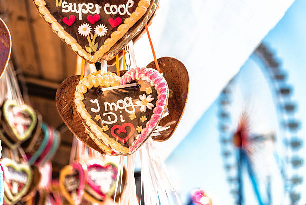 octoberfest gingerbread hearts hanging in front of ferris wheel stock photo