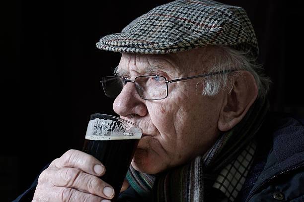 dass er trinkt ein glas bier - schiebermütze stock-fotos und bilder