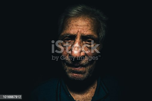 Close up portrait of an old man (octogenarian) with a serious worried expression on his face. Low key portrait of a man. Dramatic lighting.