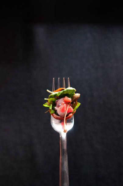 oktopus-carpacio mit zitrusfrüchten spinat salat pesto balsamico-dressing auf silber gabel, isoliert auf dunklem hintergrund - carpaccio salat stock-fotos und bilder