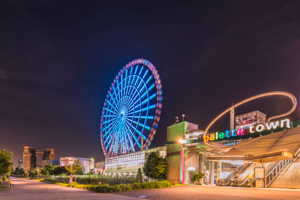 Odaiba illuminated Palette Town Ferris wheel named Daikanransha visible from the central urban area of Tokyo in the summer night sky. Passengers can see the Tokyo Tower, the twin-deck Rainbow Bridge, and Haneda Airport, as well as central Tokyo during the stock photo