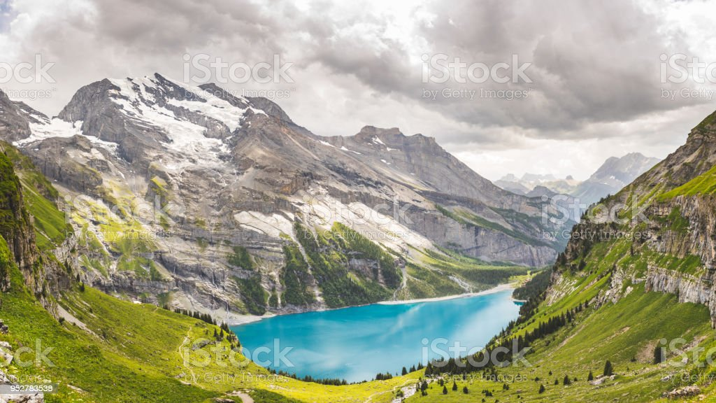 Oeschinen Lake in Swiss alps, clouds in the sky stock photo