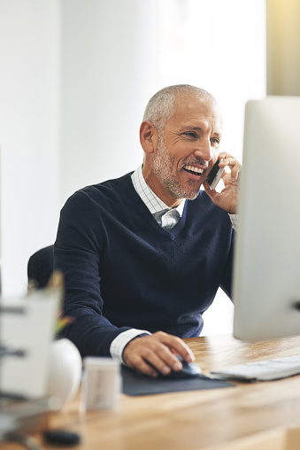 Cropped shot of a mature businessman talking on his cellphone while using a computer