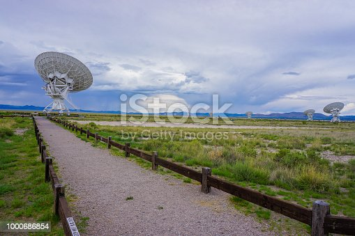 A storm lashes the distan hills with rain while in the foreground are the enormous dishes of the Very Large Array