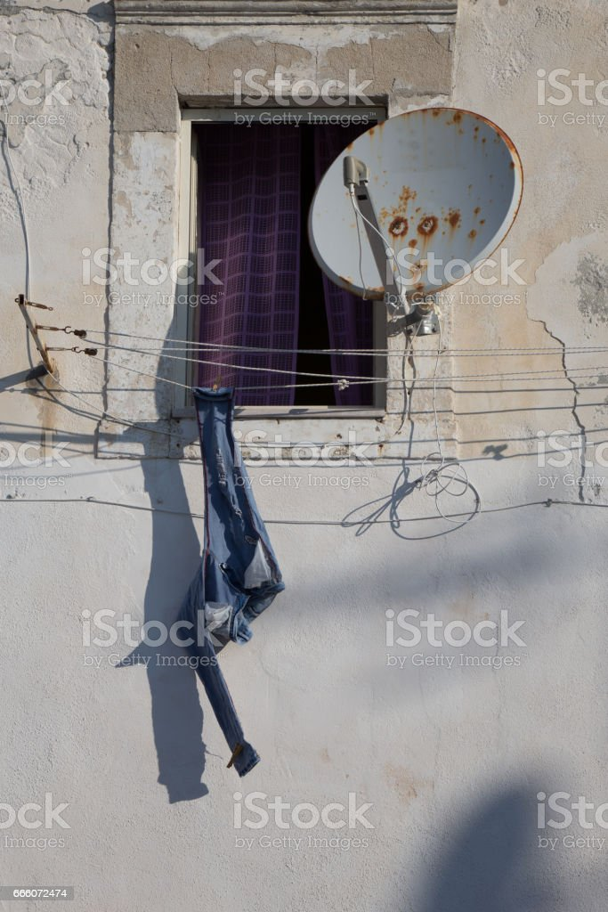 Of the threadbare old jeans hanging to dry near a television satellite dish blighted. stock photo