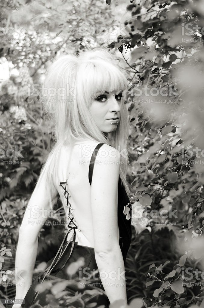 B&W of woman with cinched corset piercing in garden. stock photo