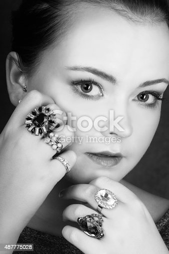 Vertical B&W studio shot on gray of young woman with big eyes and many rings on both hands. Touching cheek with one hand and chin with other, fingers curled in. Serious but open expression, head and shoulders, front view.