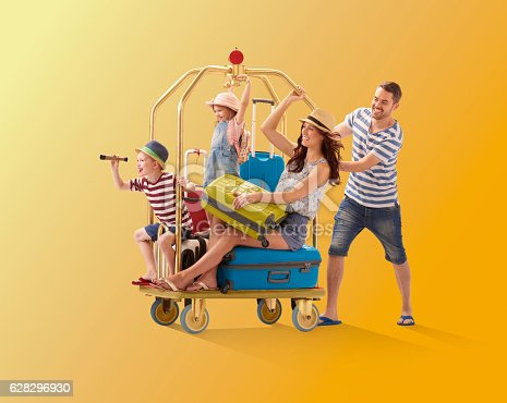 a young family climb aboard a luggage trolley and dad pushes them off to their holiday destination . They are all wearing warm weather clothing and holding their suitcases.