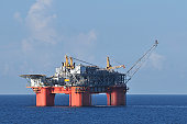 A floating deep water semi-submersible off shore oil production  platform with flare stack. An off shore oil rig.