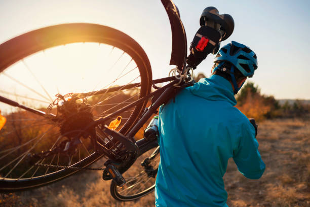 Off the beaten path Rear view of a mountain biker carrying a bicycle on his shoulder over the nature trail. mountain biking stock pictures, royalty-free photos & images