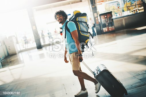 Closeup side view of a mid 20's African american guy carrying a suitcase and a backpack while walking through a train/bus station or airport. He's looking at the camera and smiling.