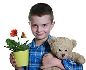 Off out to visit family, taking along a plant as a gift, but also bringing along his favourite teddy bear. Boy is 8 years old. He is happy and cheerful.