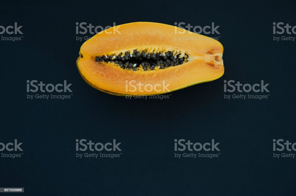 Off-centered half of tropical papaya fruit, positioned on the top center part of the image - foto de stock
