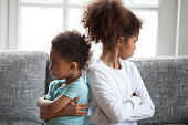 Offended African American siblings sitting ignoring, turning away from each other with arms crossed, bad relationships between little preschooler sister and toddler brother, children conflict