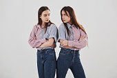 Offended and look at other with anger. Two sisters twins standing and posing in the studio with white background.