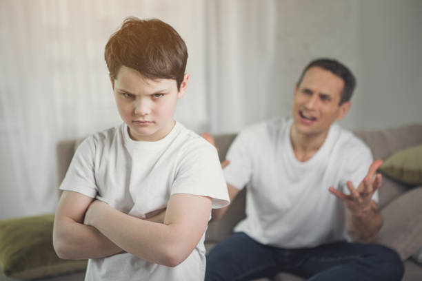 Offended child hearing irritated dad shouting stock photo