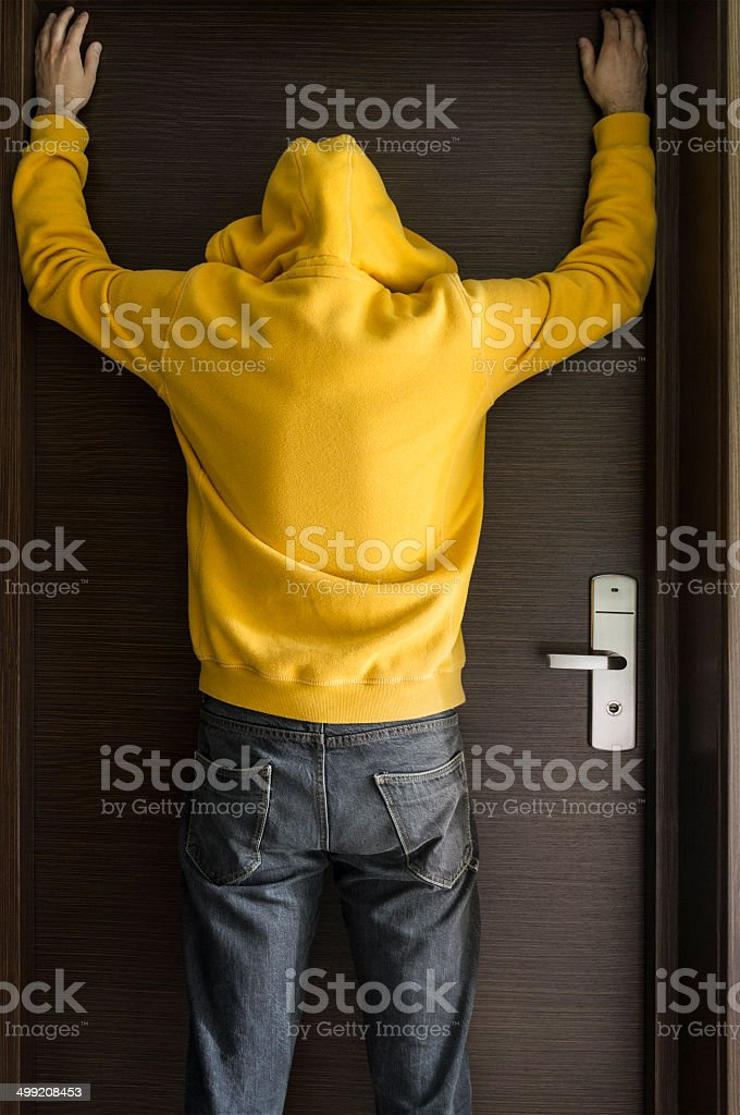 Offender, burglar in yellow hoodie is standing with arms raised in...