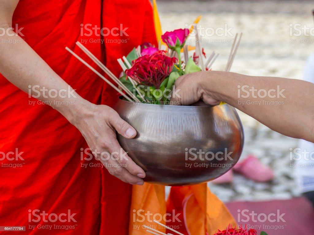 Offer sacrifice flowers to monk stock photo