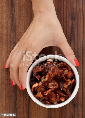 Woman hand holding bowl full of fried bacon