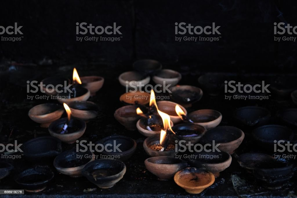 Offering Lit Candles In Dark Buddhist Sacrificial Altar