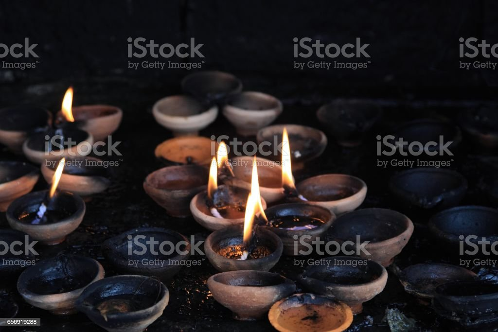 Offering lit candles in dark buddhist sacrificial altar stock photo