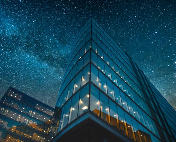 office building bei nacht - fensterfront stock-fotos und bilder