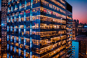 Office building at night with illuminated windows.