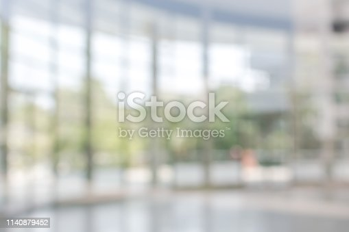 Blur background interior view looking out toward to empty office lobby and entrance doors and glass curtain wall