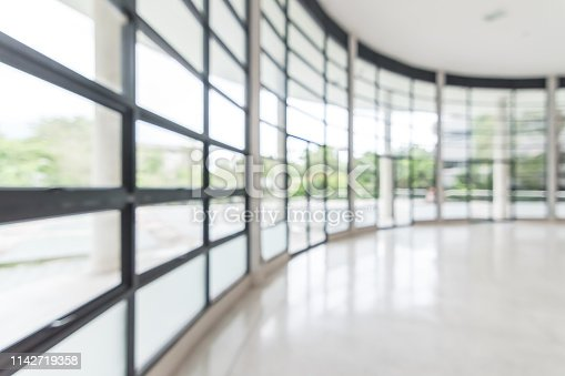 990877026 istock photo Office building business lobby blur background with blurry glass window transparent wall interior view inside empty entrance hall 1142719358