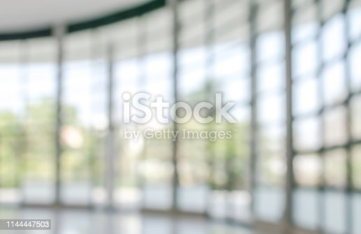 990877026 istock photo Office building business lobby blur background with blurry glass window transparent wall interior view inside empty entrance hall 1144447503