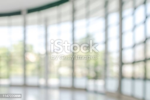 990877026 istock photo Office building business lobby blur background with blurry glass window transparent wall interior view inside empty entrance hall 1147220998