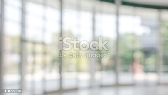 990877026 istock photo Office building business lobby blur background with blurry glass window transparent wall interior view inside empty entrance hall 1148727455