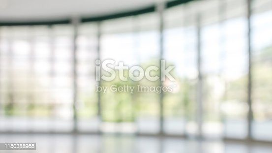 990877026 istock photo Office building business lobby blur background with blurry glass window transparent wall interior view inside empty entrance hall 1150388955