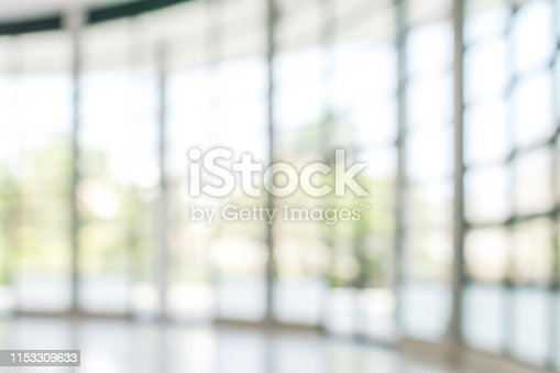 990877026 istock photo Office building business lobby blur background with blurry glass window transparent wall interior view inside empty entrance hall 1153309633