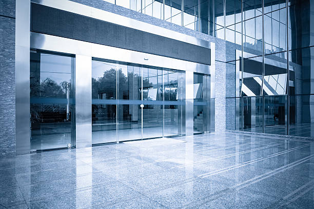 office building entrance and automatic glass door modern office building gate entrance and automatic glass door with blue tone automatic stock pictures, royalty-free photos & images