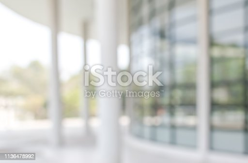990877026 istock photo Office building lobby or university entrance hall blur background with blurry exterior view of glass window and wall with light bokeh 1136478992