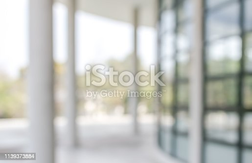 990877026 istock photo Office building lobby or university entrance hall blur background with blurry exterior view of glass window and wall with light bokeh 1139373884