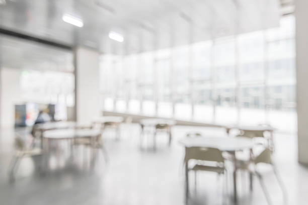 Office building or university lobby hall blur background with blurry school hallway corridor interior view toward empty corridor entrance, glass curtain wall, floor and exterior light illumination stock photo