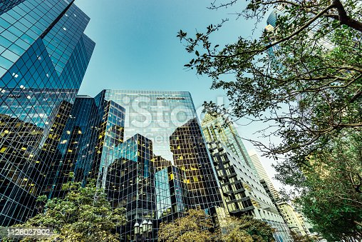 Glass office buildings among green trees