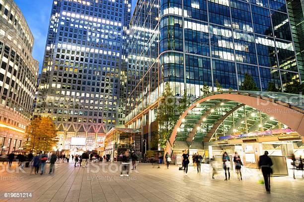 There are several people walking through the business district of a city at dusk, blurred by the slow camera exposure, blurred motion, horizontal orientation,Canary Wharf, London, England, UK.