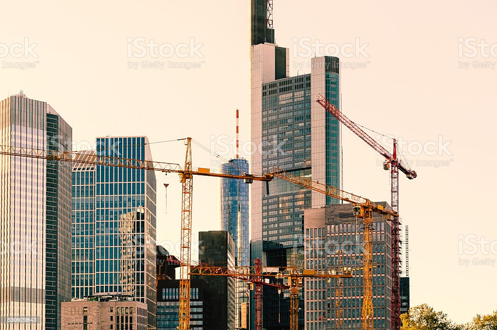 Office buildings behind construction cranes at sunset stock photo