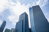 Office Buildings In The Sky. Looking Up At Modern Corporate Buildings On A Sunny Day, With Dramatic Clouds. Stock Photo.