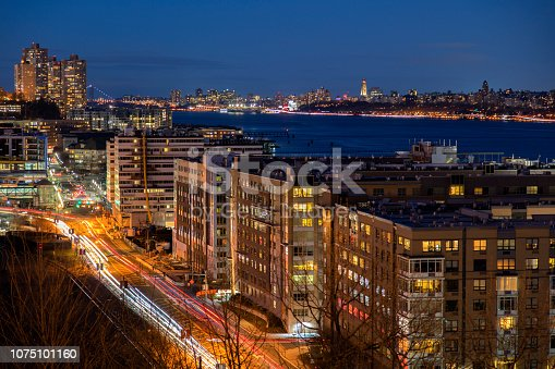 Illuminated street and modern office buildings on the banks of the Hudson River in New Jersey, Manhattan is visible on the right side, HDR image.