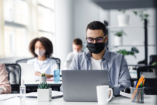 Office center workers are protected from virus outbreak during covid-19 epidemic. Young hipster man in glasses and protective mask works at laptop, with colleagues at workplaces in interior, free space