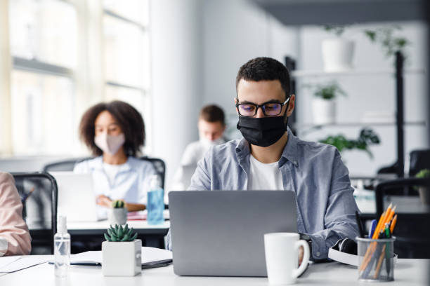 Office center workers are protected from virus outbreak during covid-19 epidemic. Young hipster man in glasses and protective mask works at laptop stock photo