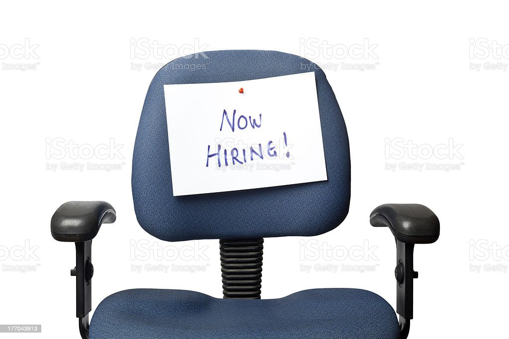Office chair with hand written 'NOW HIRING!' sign on back stock photo