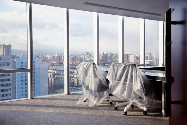 Office chairs covered in bubble wrap in modern office studio View of contemporary modern glass wall meeting room office chairs bubble wrapped in skyscraper high above city urban downtown with bright natural light daylight sunshine and high back design furniture corner office business aspirations weather dawn dusk afternoon sunset sunrise spiritual religious aspirations opportunity the way forward city life simplicity dreams reminiscent community order organization population empty desk stock pictures, royalty-free photos & images